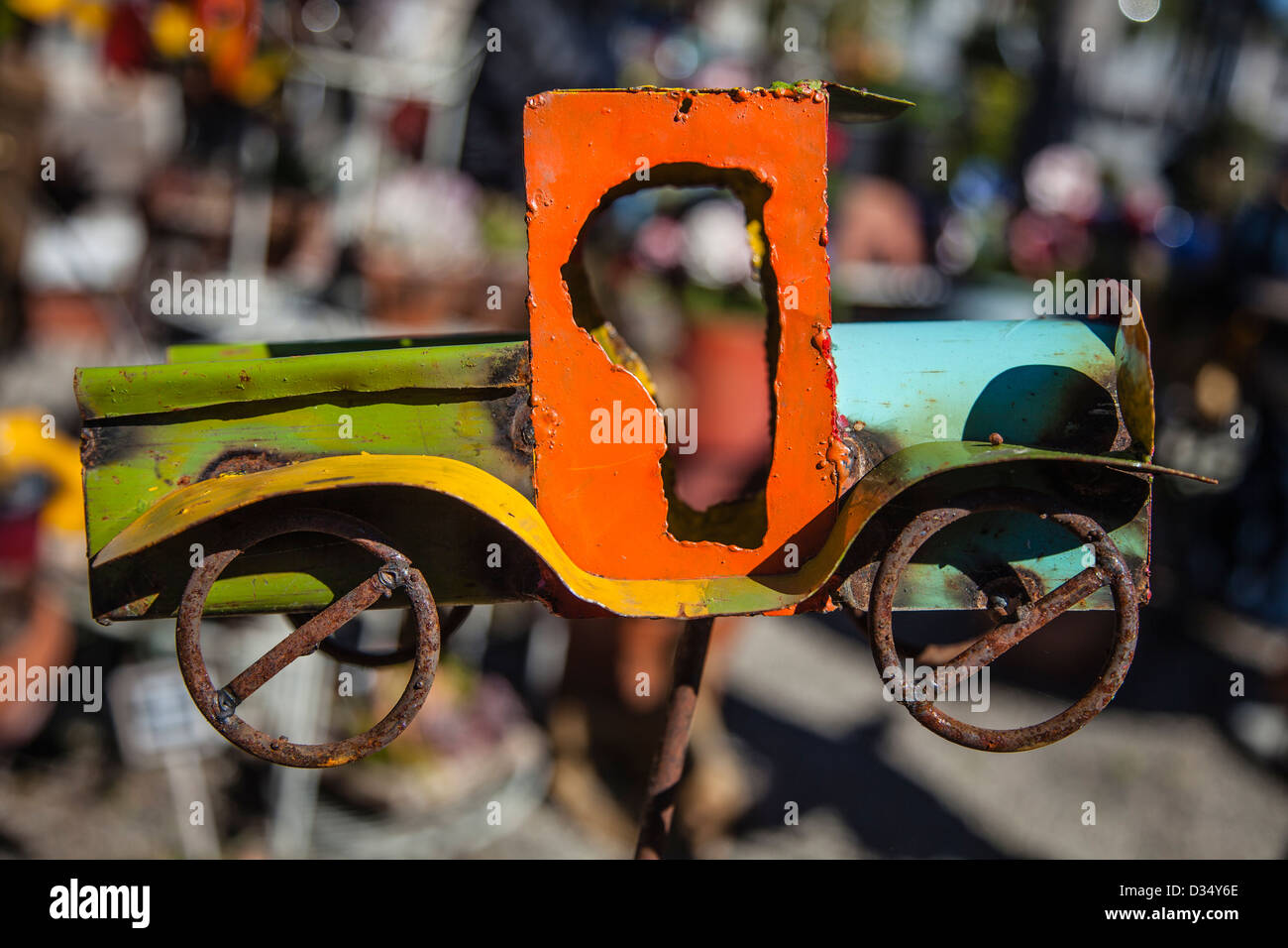 A multicolored primitive toy truck on a rusted metal rod created for placement in a garden. - Stock Image