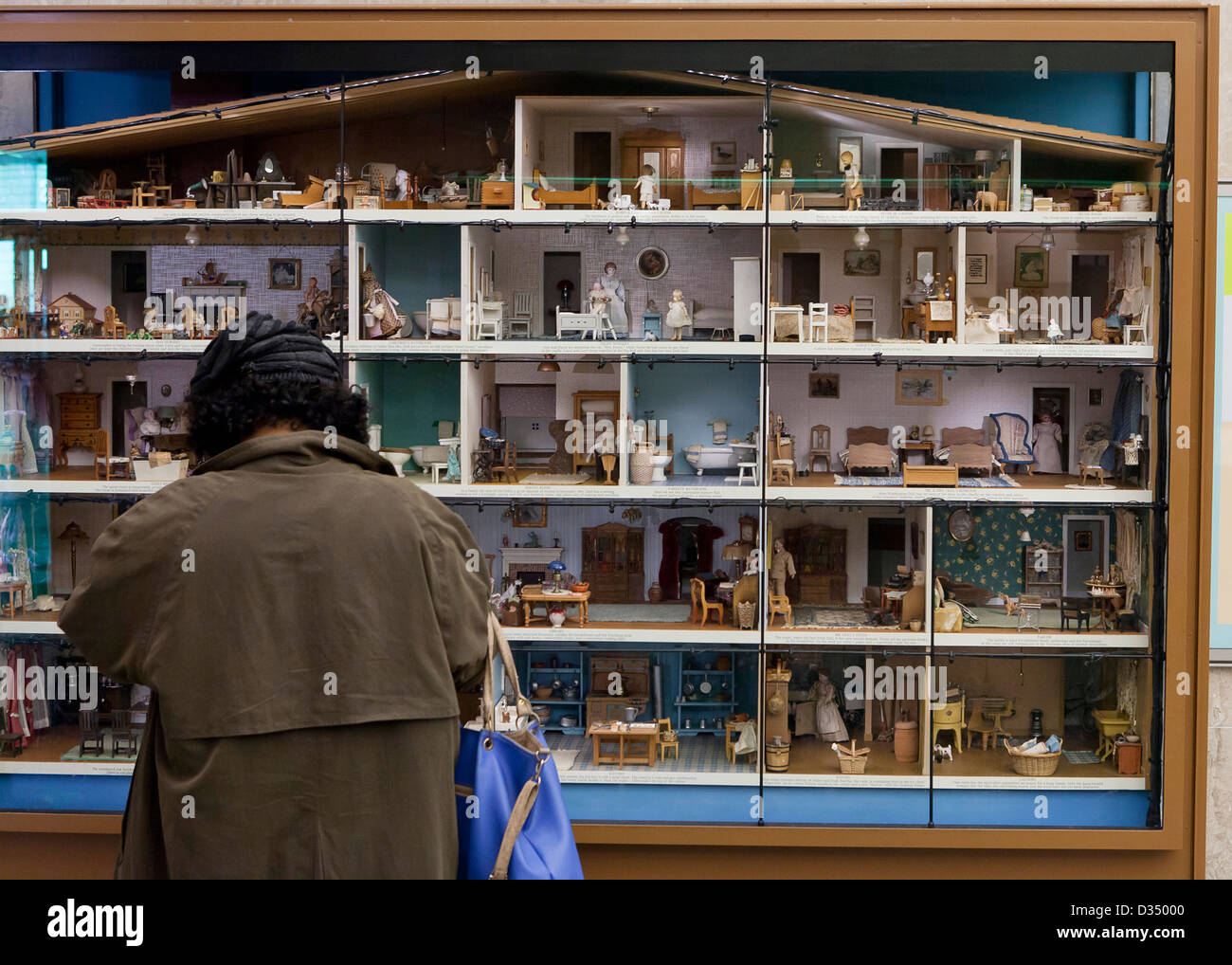 Woman looking at a large, multistory dollhouse - Stock Image