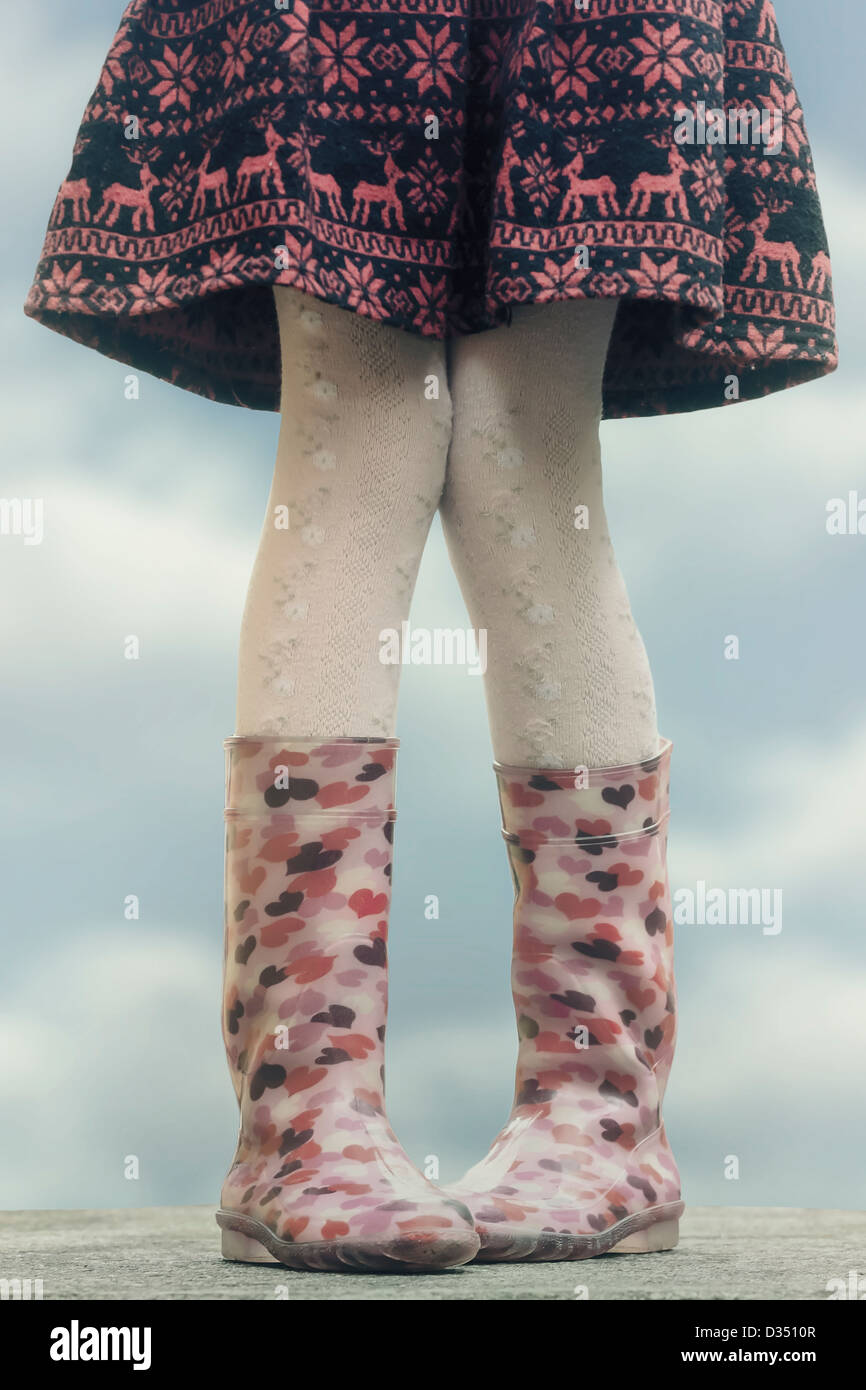 a girl in wellies on a table - Stock Image
