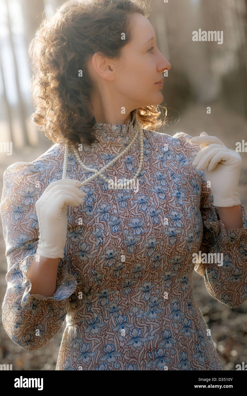 a woman in a vintage dress with gloves and a pearl necklace - Stock Image
