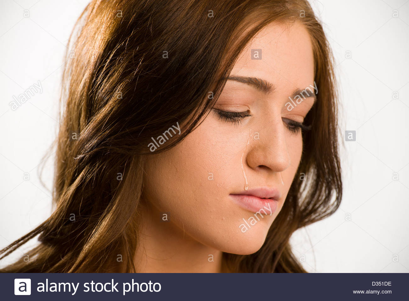Closeup of a young woman with tears on her face. She is looking down. - Stock Image