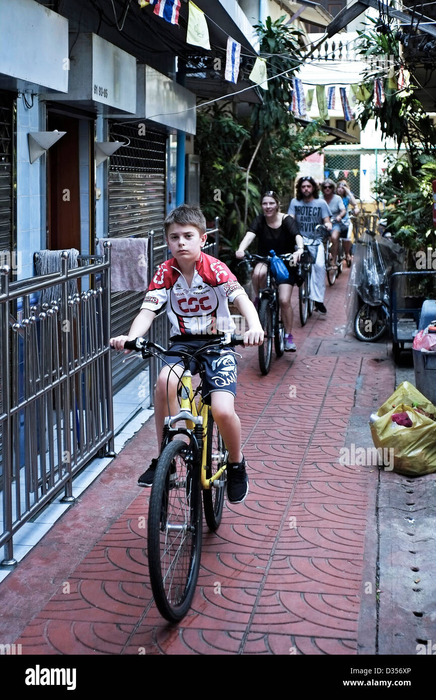 A group of cyclists on an organised tourist bicycle tour of Bangkok side streets. Thailand S. E. Asia - Stock Image