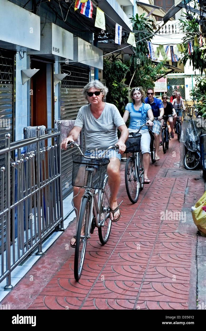 A group of cyclists on an organised bicycle tour of Bangkok side streets. Thailand S. E. Asia - Stock Image