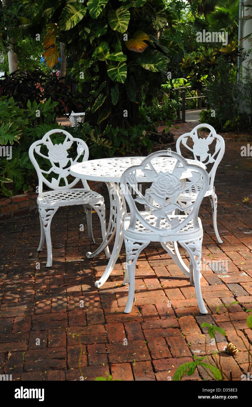white ornamental garden chairs in a backyard patio with surrounding garden - Stock Image