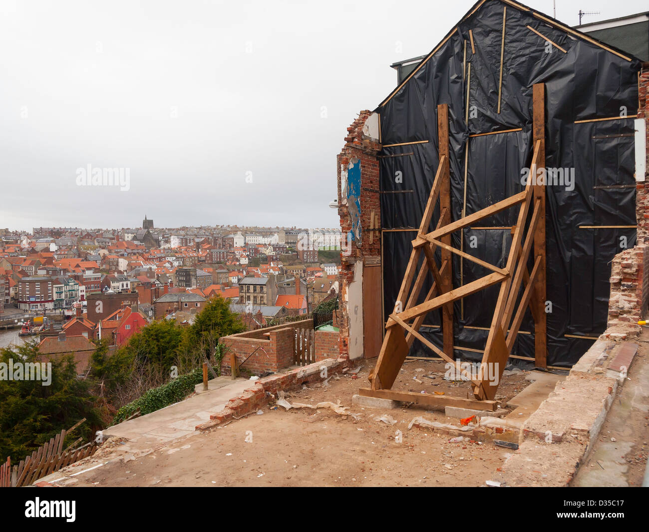 Timber shoring supports a remaining cottage in Aelfleda Terrace Whitby after landslip necessitated demolition of - Stock Image