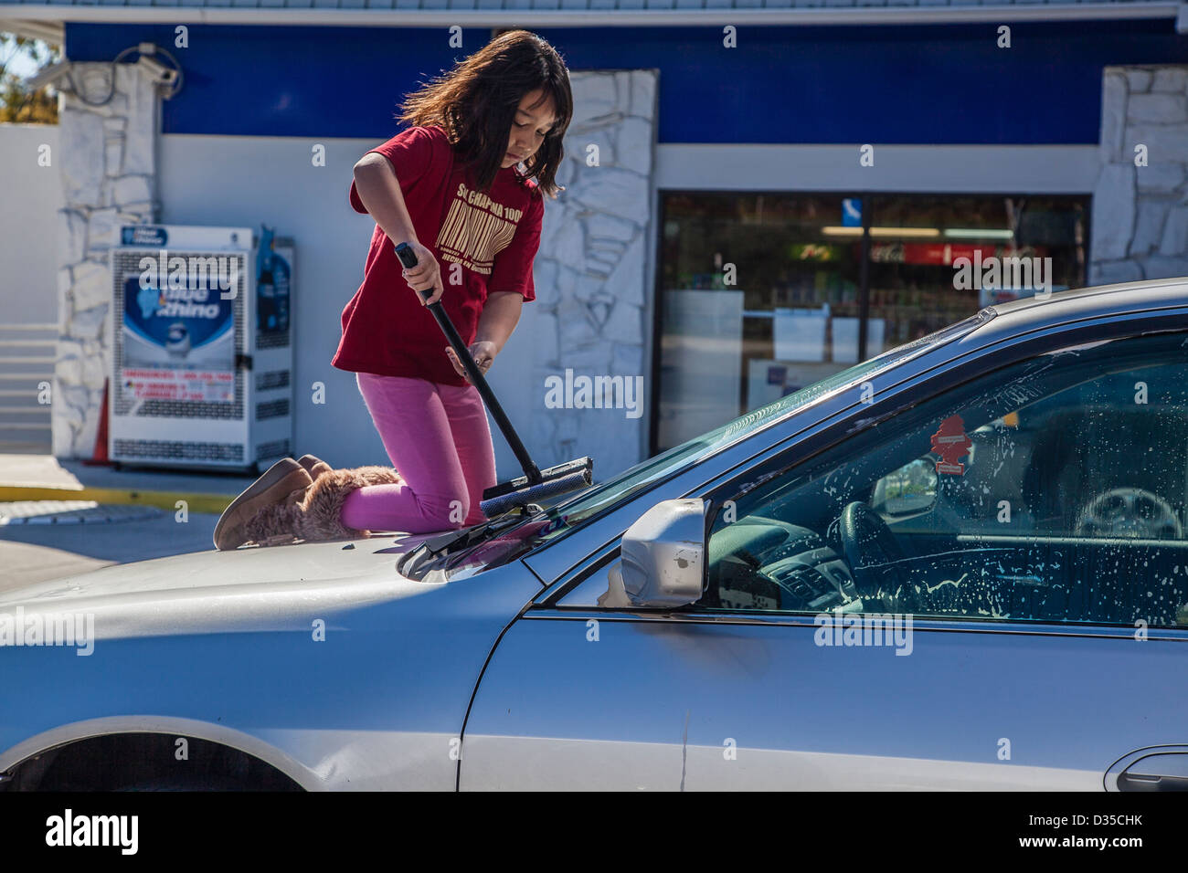 An 8-10 year old Hispanic girl kneels on the hood of her mother's car and washes the windshield with a squeegee. - Stock Image