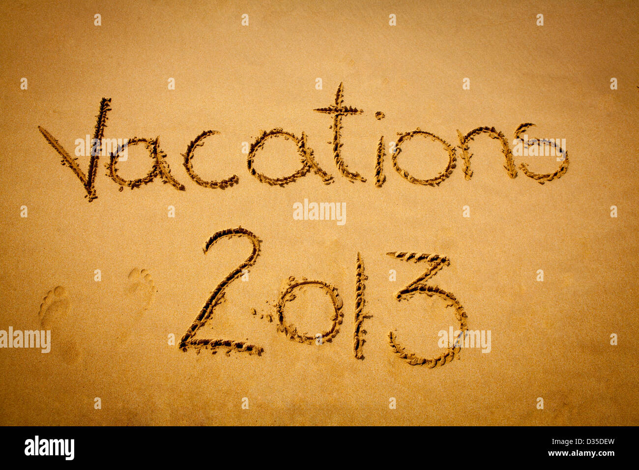 Vacations 2013 written on sand - tropical beach - Stock Image