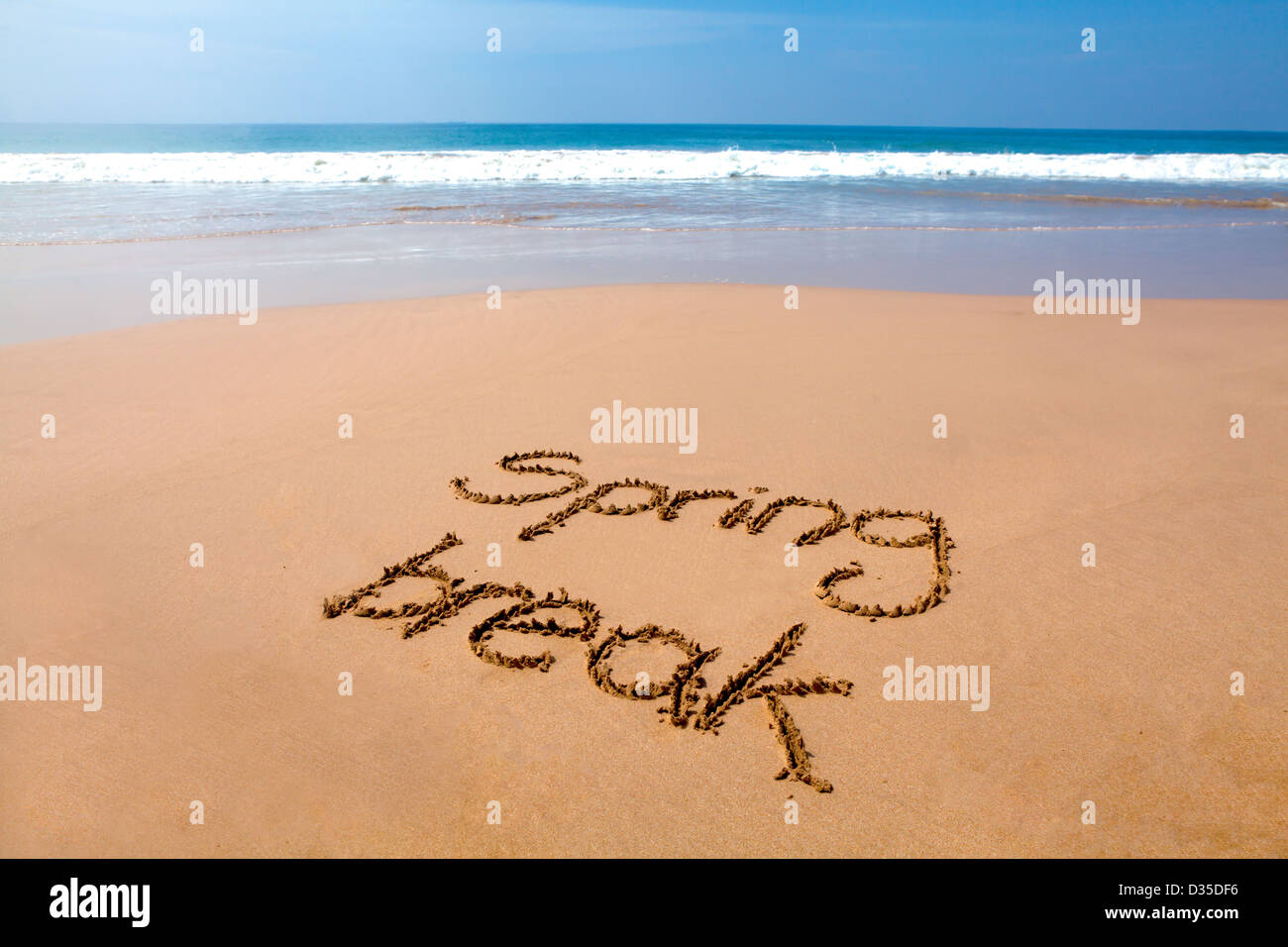Words spring break written in sand on a tropical beach, with sea in background - Stock Image