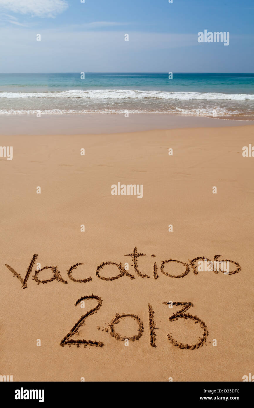 Words 'Vacations 2013' written in sand on tropical beach - Stock Image