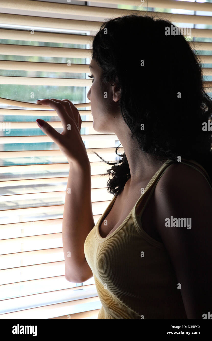 Attractive young dark haired female looking out through a wooden blind. - Stock Image