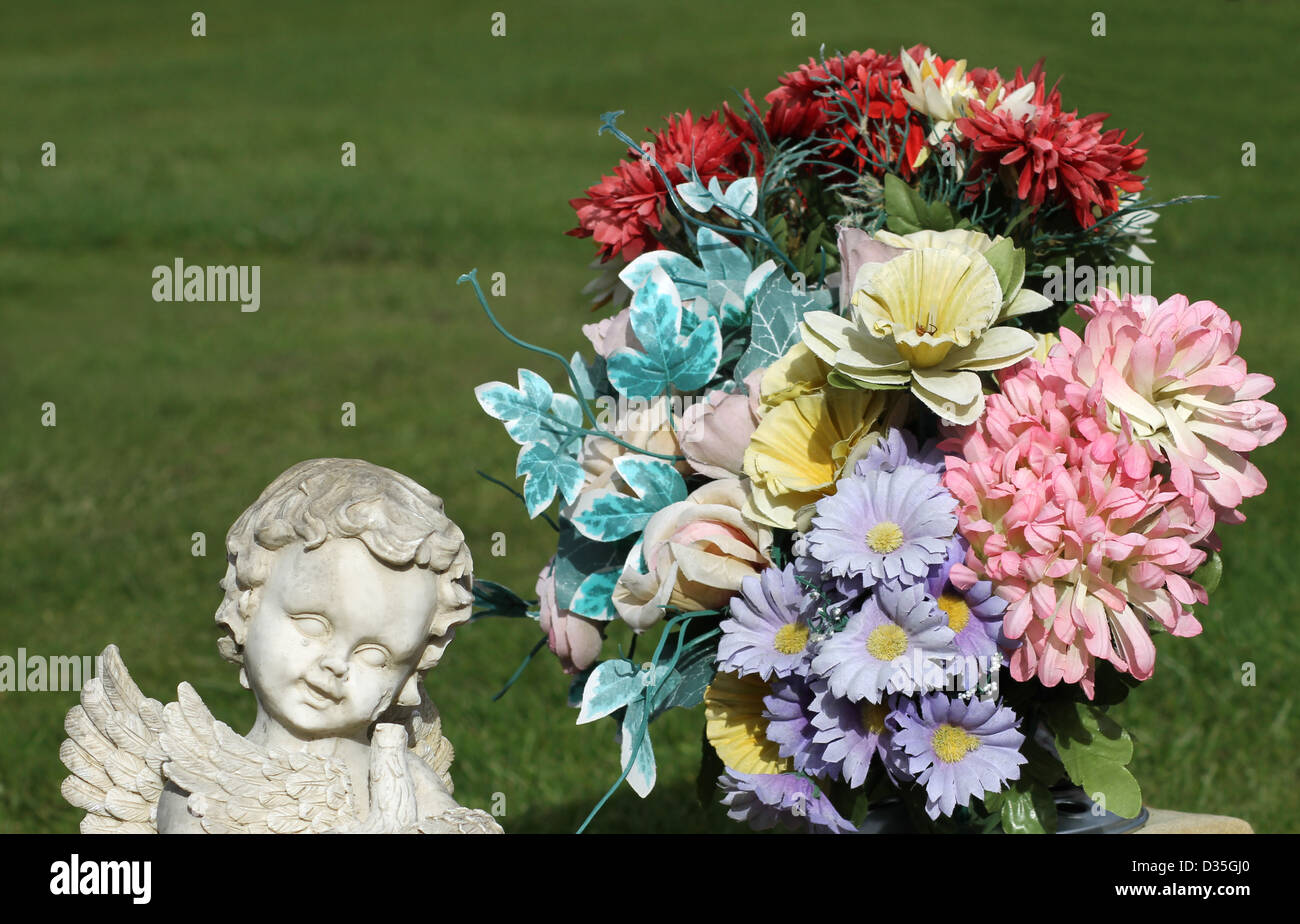 Angle statue in cemetery next to bouquet of flowers. Grass in background with copy space. - Stock Image