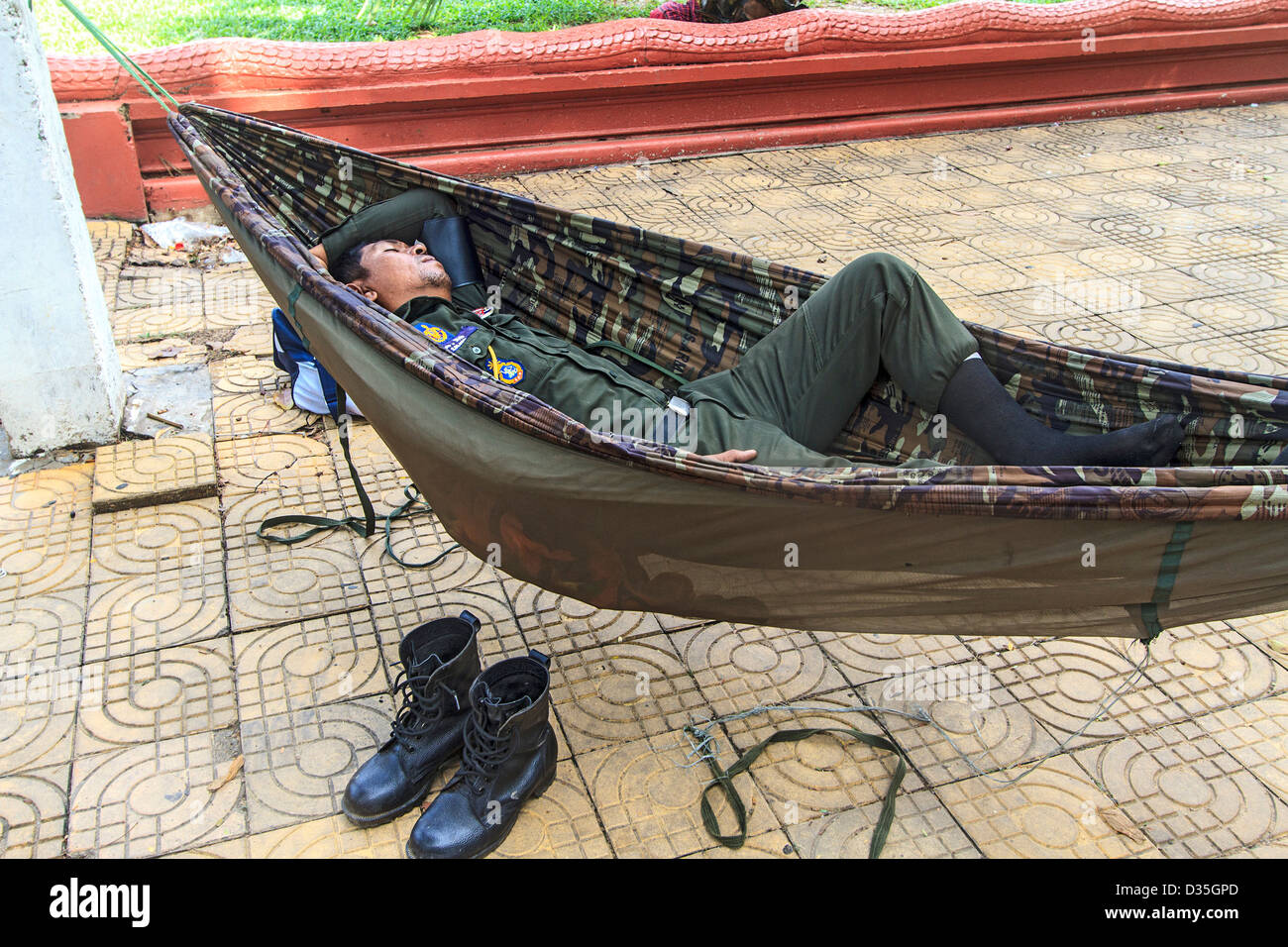 Military policeman naps in hammock, Phnom Penh, Cambodia. - Stock Image