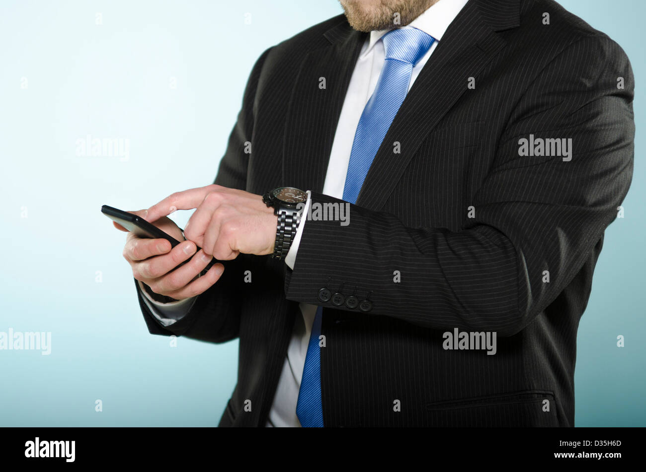 Businessman using smart phone. Middle section of casually suited man using a touch screen phone with his finger. - Stock Image