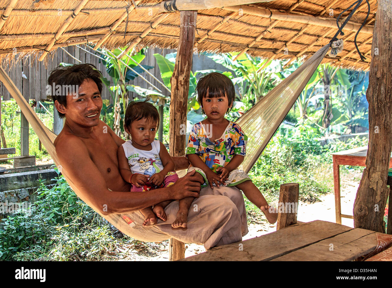 Young father and his daughters in a hammock, Kratie, Cambodia - Stock Image