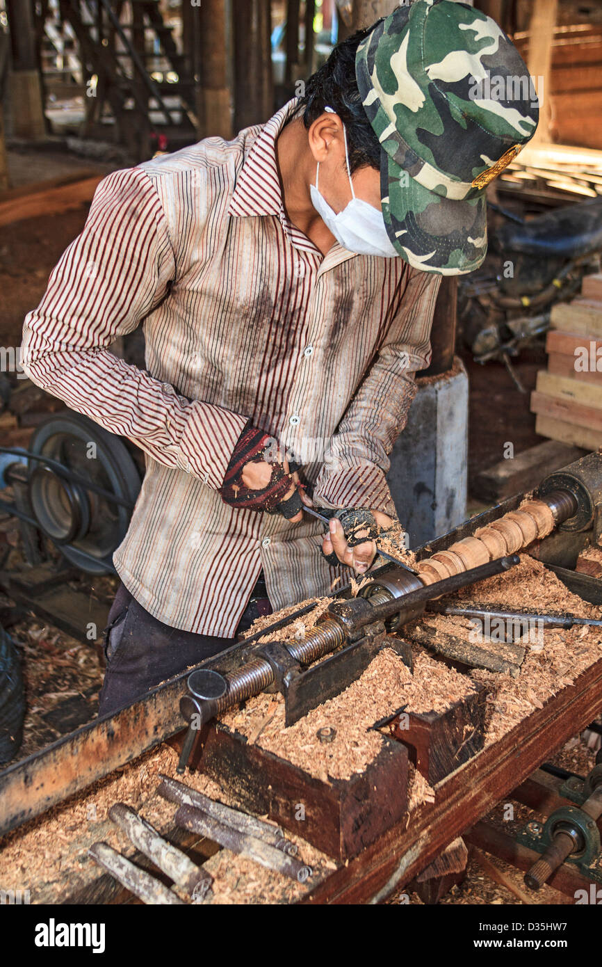 Man uses lathe to shape posts in a Cham village along the Mekong River south of Kratie, Camboda - Stock Image