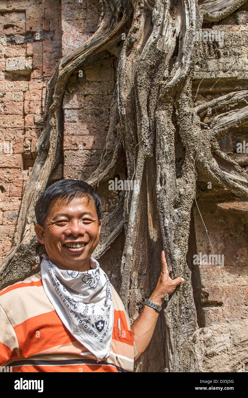 Man stands by tree root at a temple in Sambor Prei Kuk, not far from the Angkor Wat complex of ruins and temples - Stock Image