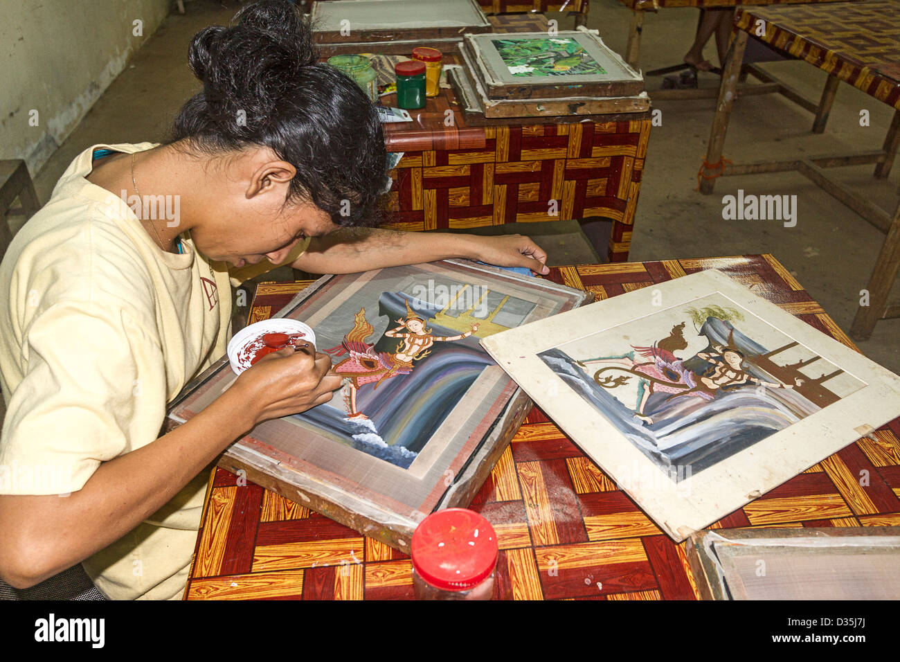 Woman works on silk painting at Artisan Angkor, a workshop that trains young, uneducated and disabled Cambodian Stock Photo