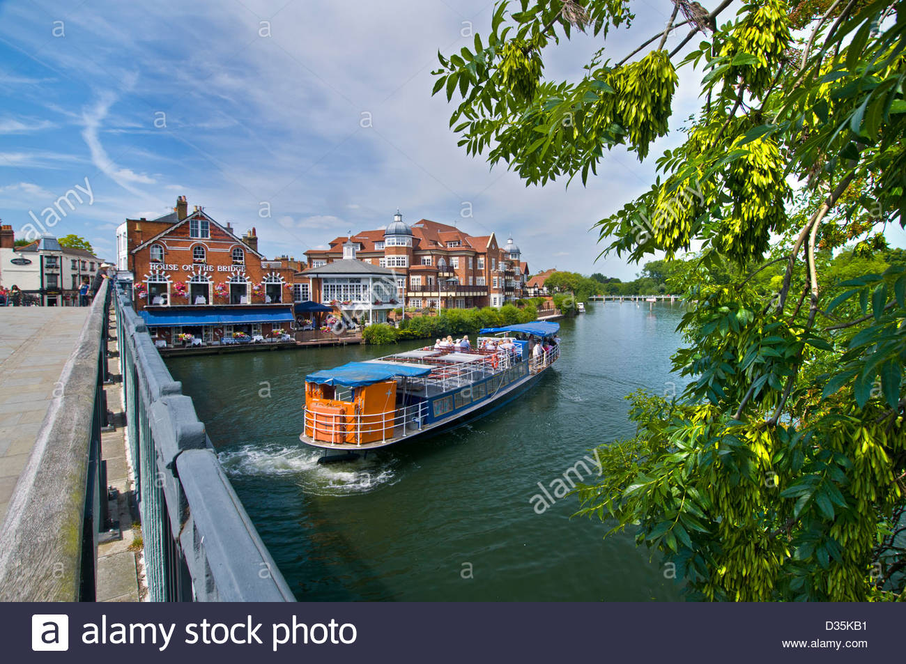 River Thames cruise boat mooring at Windsor Berkshire with village of Eaton behind UK - Stock Image
