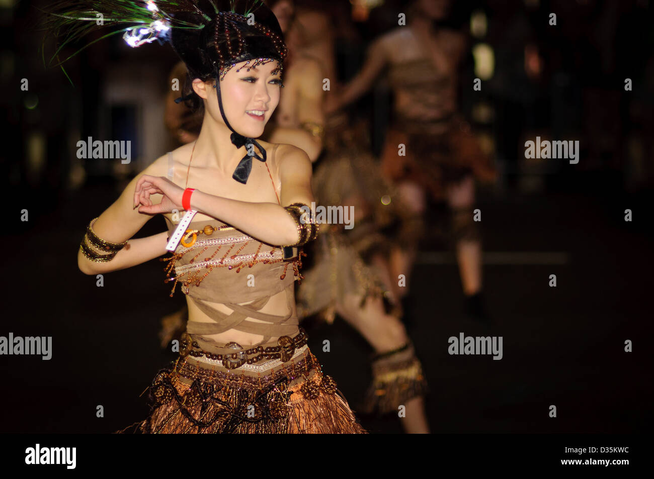 Chinese ethnic minority dancer - dancing in a parade while wearing traditional costumes. - Stock Image