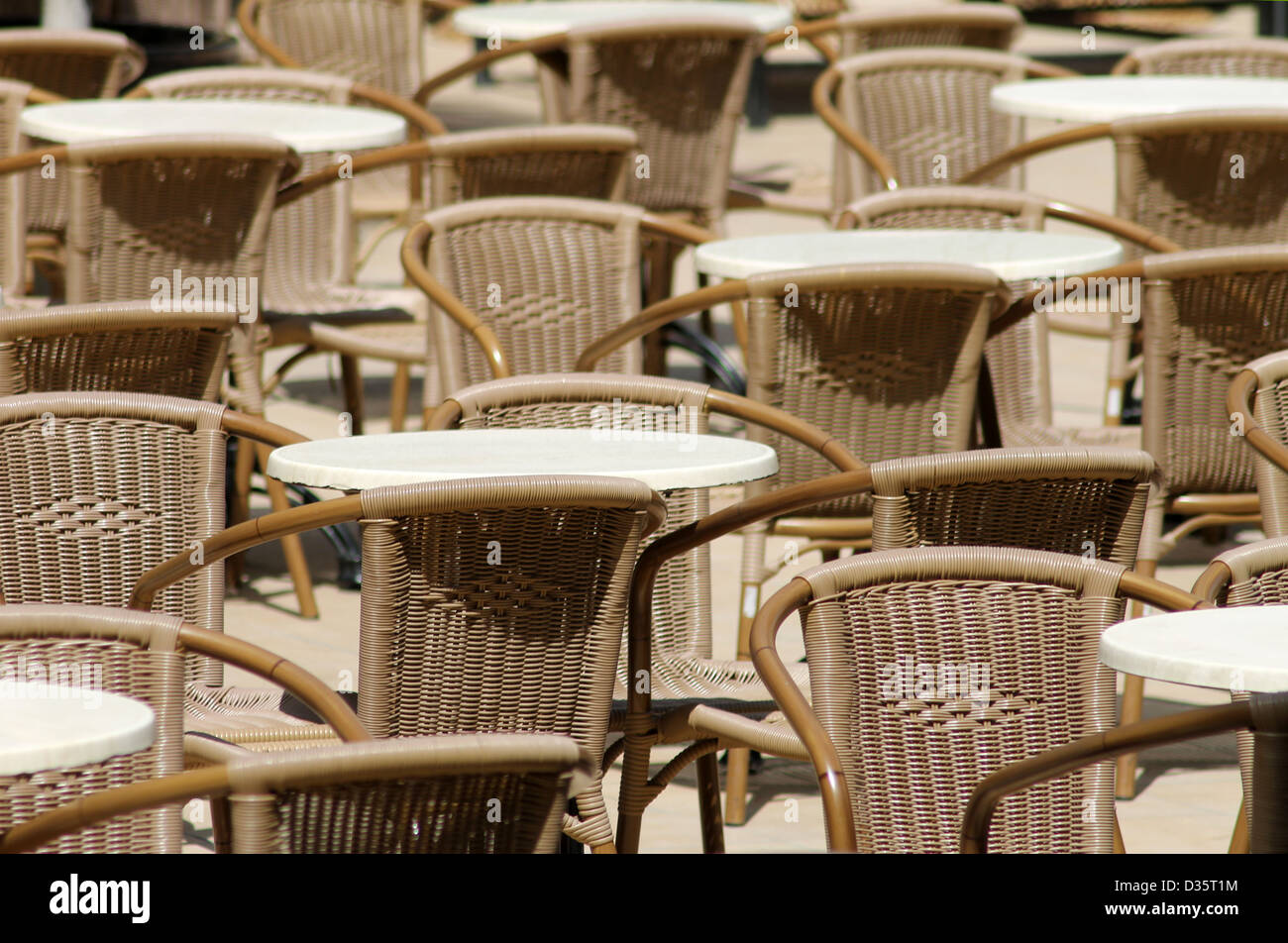 Outdoor tables and chairs in seating area. - Stock Image