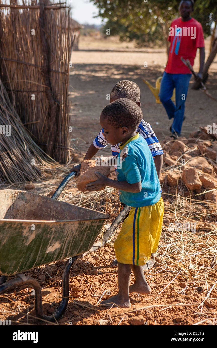 African boys helping with village work - Stock Image