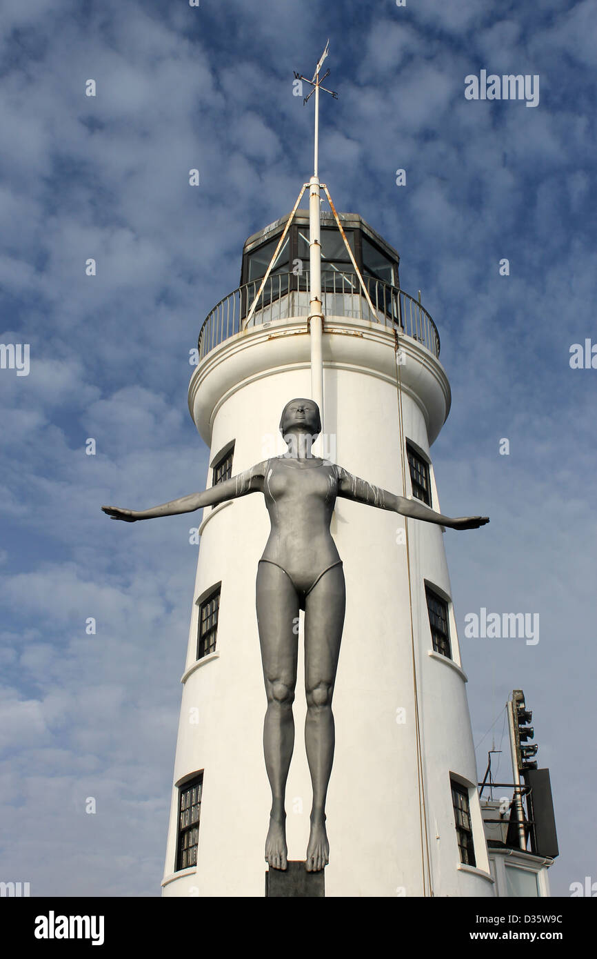 Scarborough Lighthouse with Diving Belle sculpture in foreground, England. - Stock Image