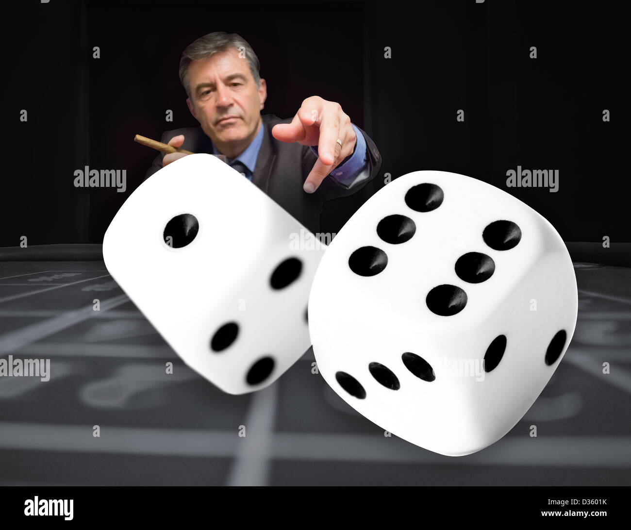 Gambler at the poker table with digital dice in foreground - Stock Image