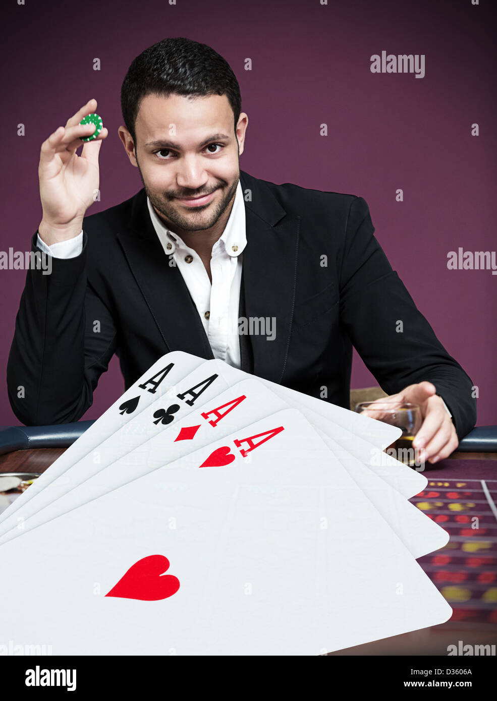 Handsome gambler betting on four aces - Stock Image