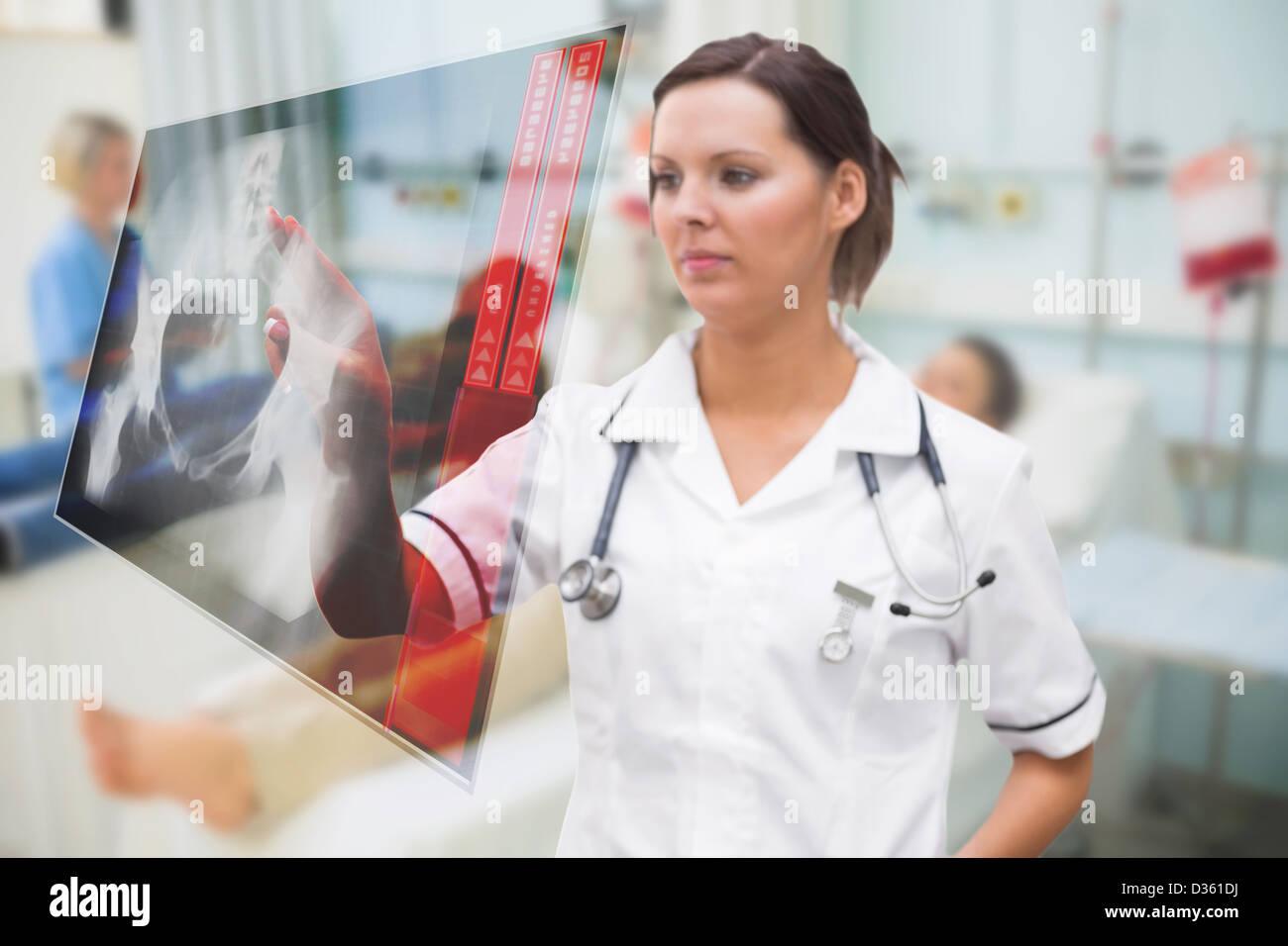 Nurse pressing on screen showing pelvic x-ray - Stock Image