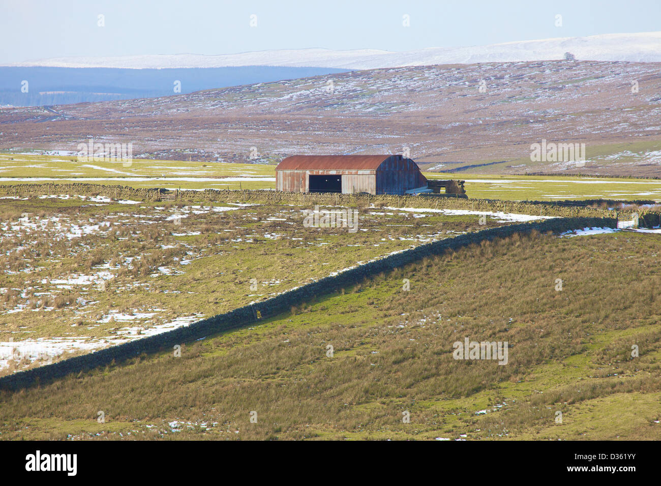 Peatrigg corrugated iron barn with snow covered hills Northumbria England United Kingdom Great Britain - Stock Image