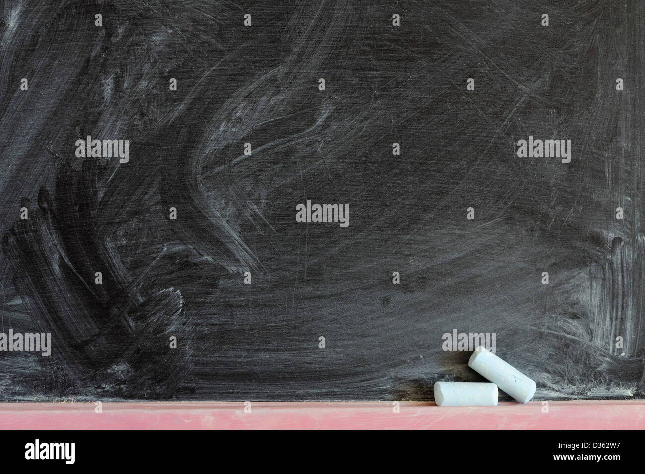 detailed black chalkboard fragment with two chalk pieces - Stock Image