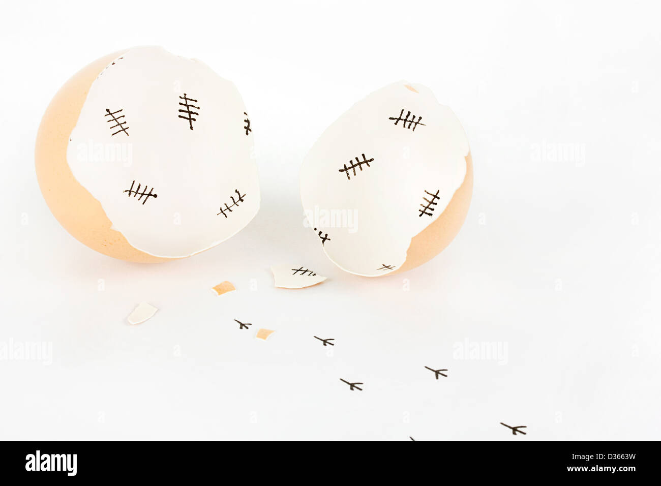 Broken egg shell with tally marks inside and chick footprints on white - Stock Image