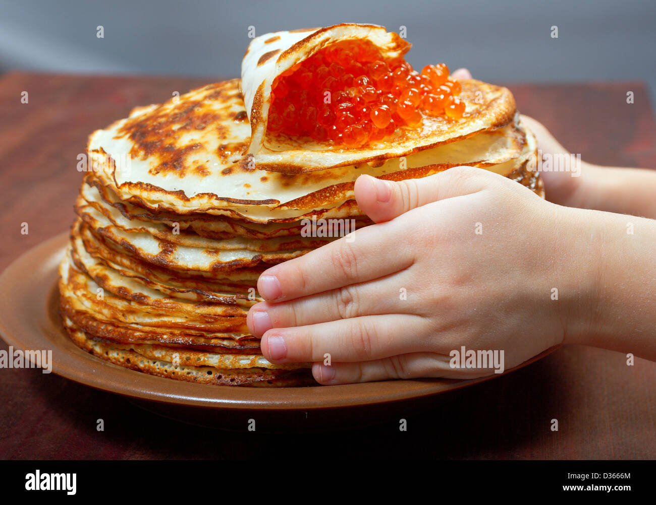 Traditional Russian pancakes with red caviar.hands child - Stock Image
