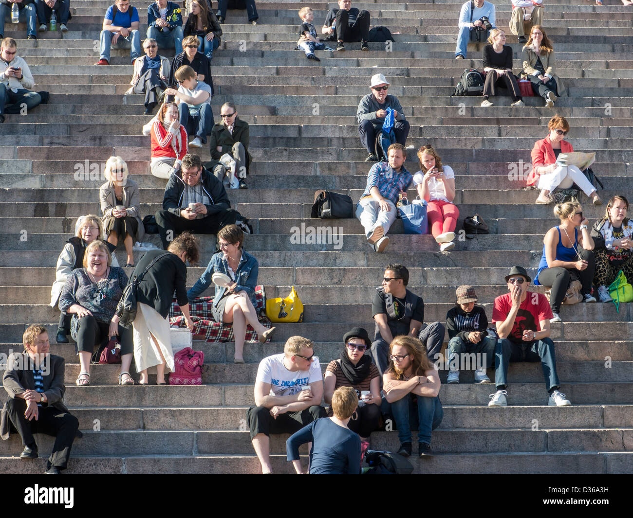 People sitting in the sun on the stone steps outside of the cathedral in Helsinki, Finland. - Stock Image