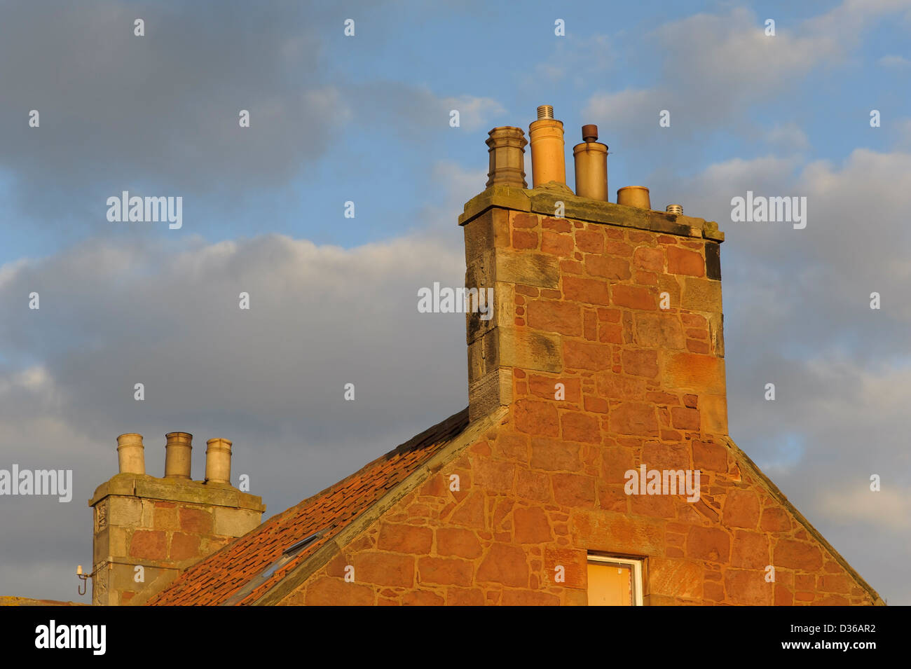 Large pottery chimney pots on a stone chimney stack of an old house in Scotland. - Stock Image