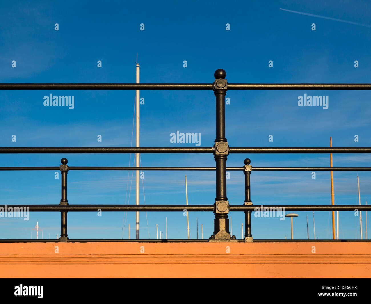 Black railings against a blue sky. - Stock Image