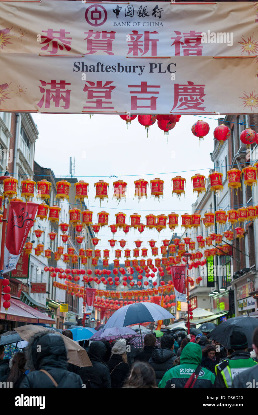 Signs lanterns and decorations with crowds under umbrellas Gerrard Street London UK at Chinese New Year Celebrations - Stock Image