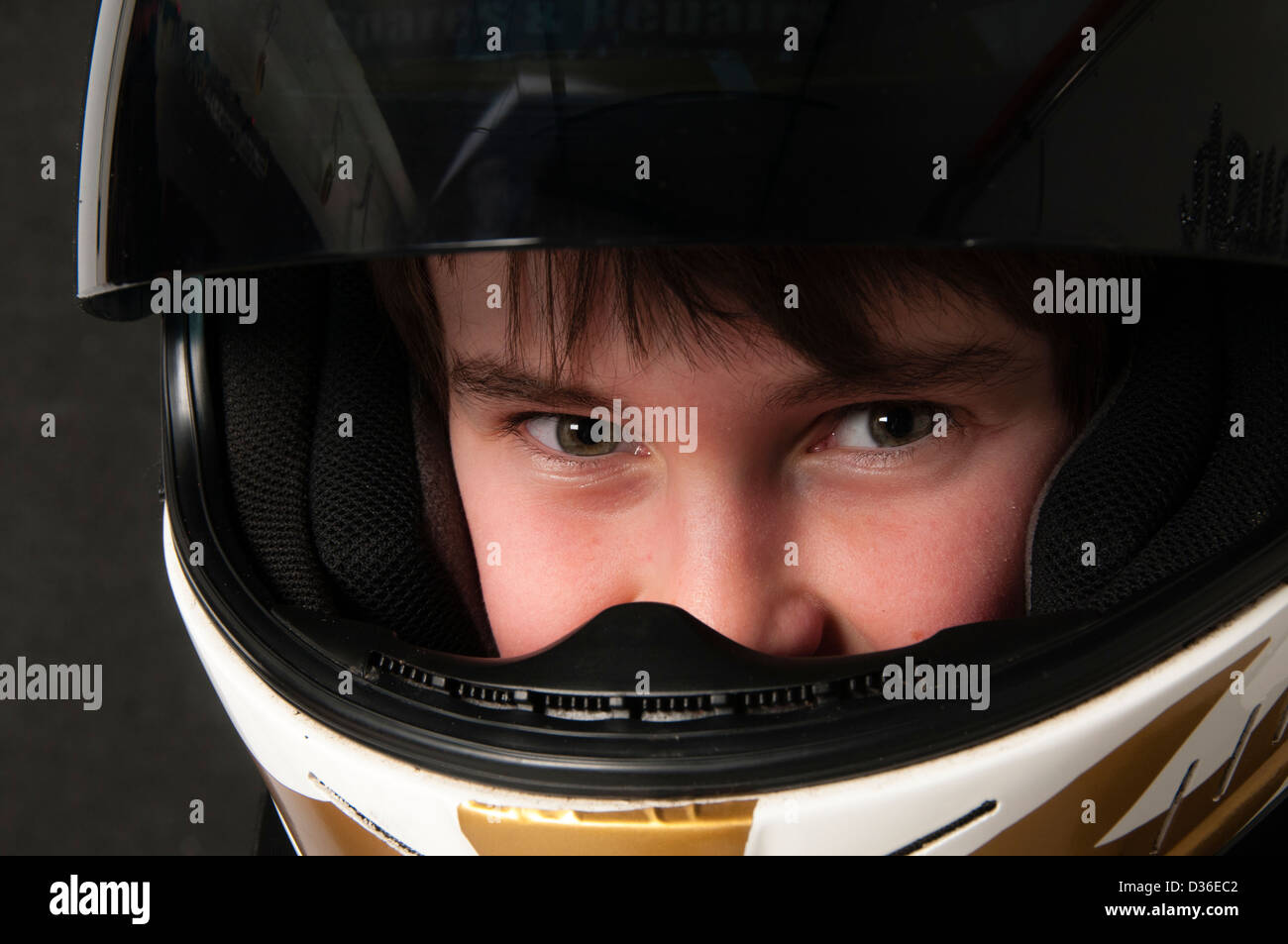 Child Wearing A Motorsport Crash Helmet - Stock Image