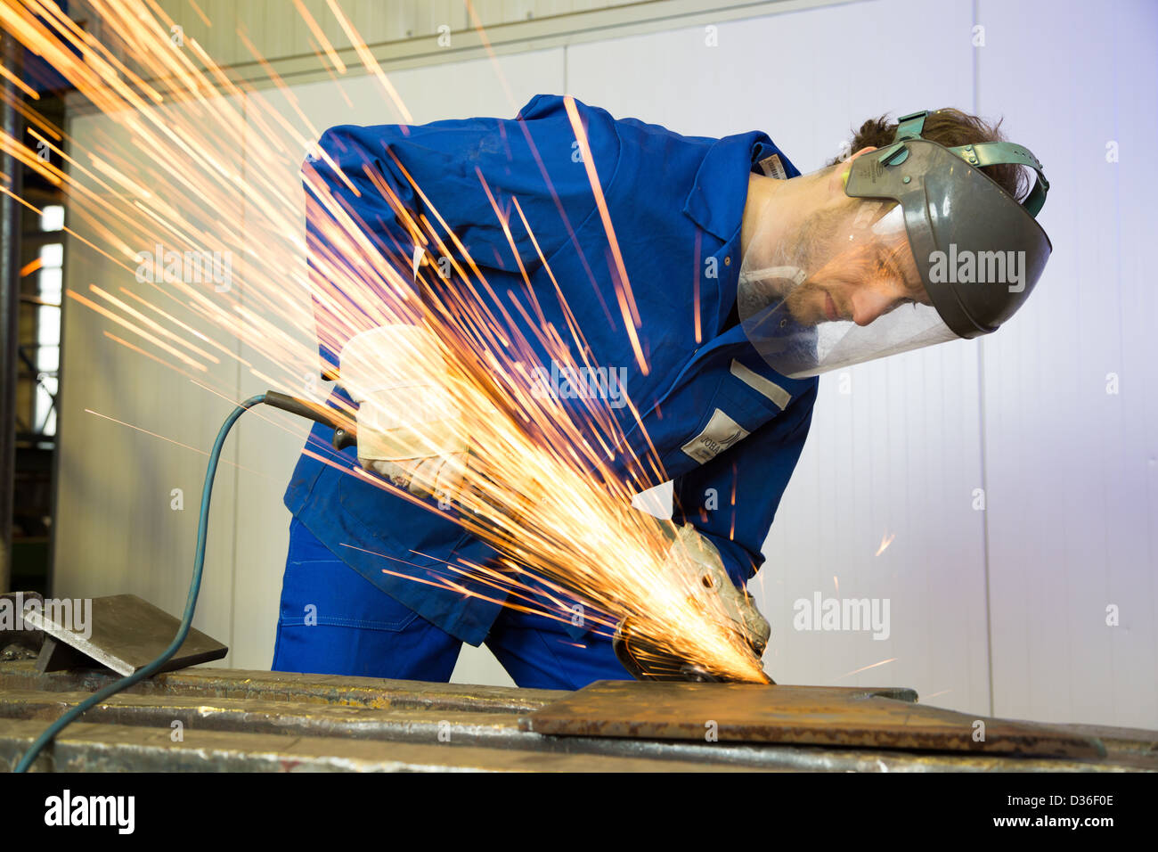 A construction worker using an angle grinder producing a lot of sparks - Stock Image