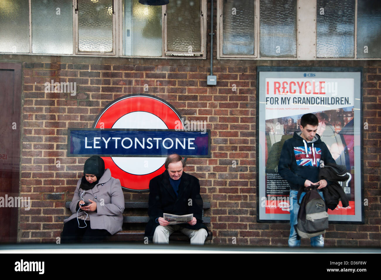Passengers waiting at Leytonstone underground station, seen from a passing tube - Stock Image