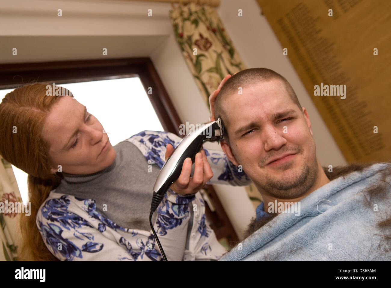 26 year old man in process of having all his hair shaved off for a cancer charity, Bordon, Hampshire, UK. - Stock Image