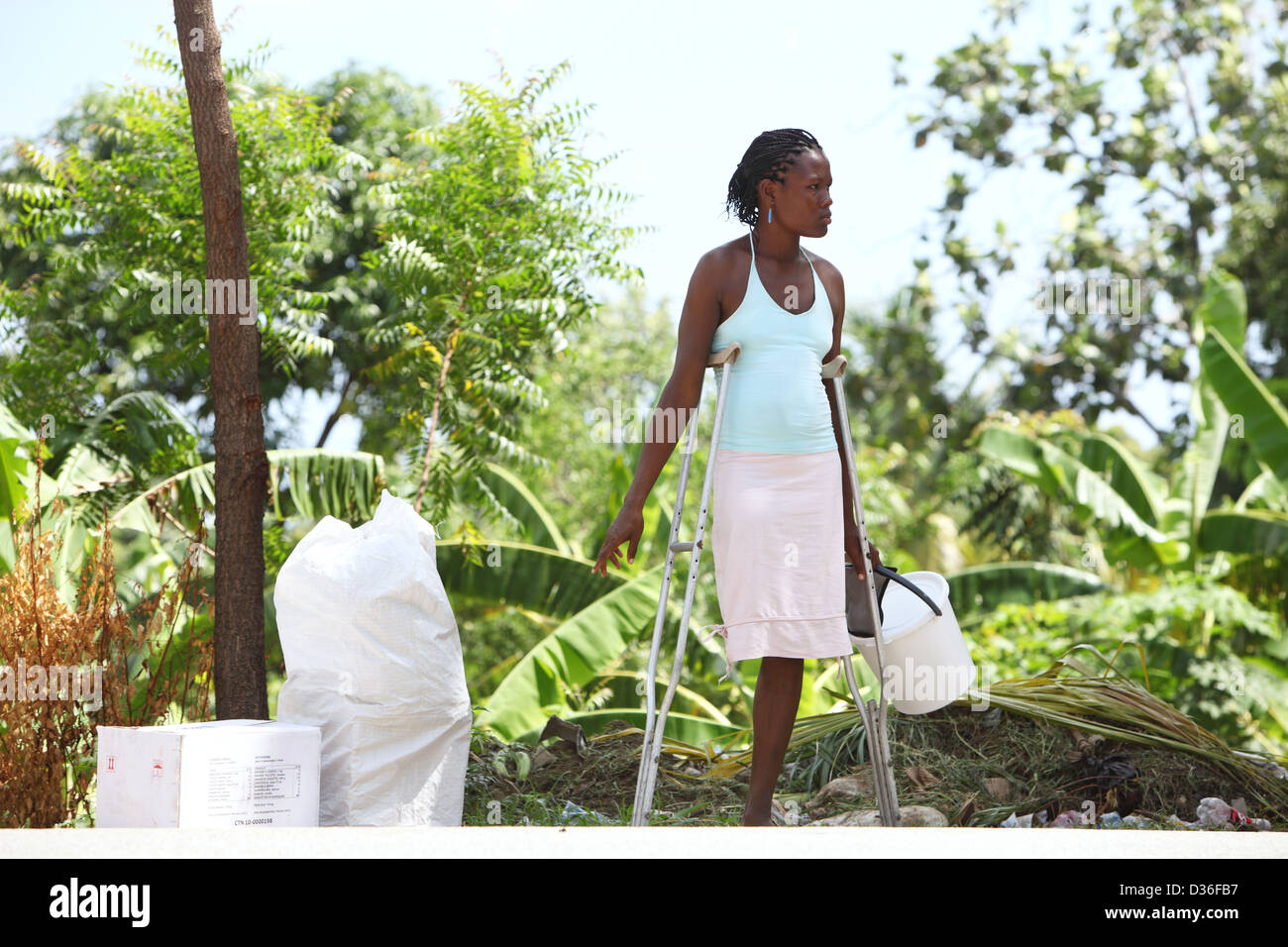 Leogane, Haiti, one leg amputee woman helps volunteers in the distribution of relief supplies - Stock Image