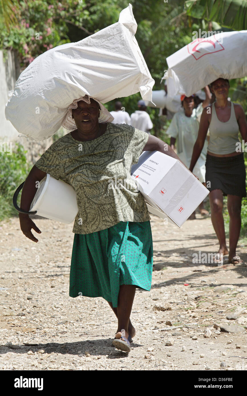 Leogane, Haiti, auxiliary volunteers carry cargoes on the head - Stock Image