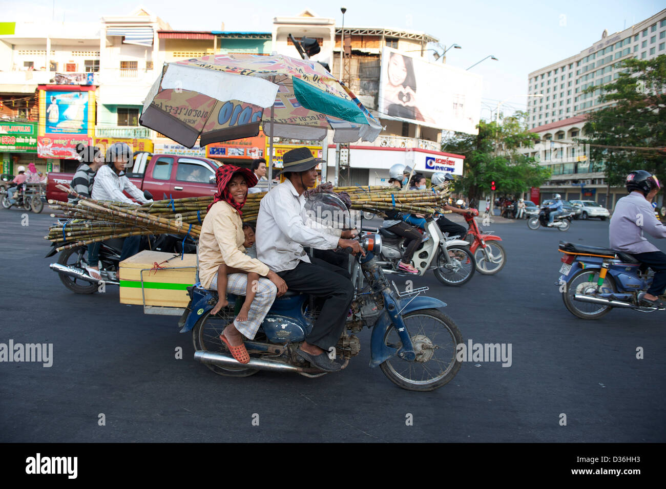 baby sleeping while being driven on a motorbike through the trafic of Phnom Penh - Stock Image