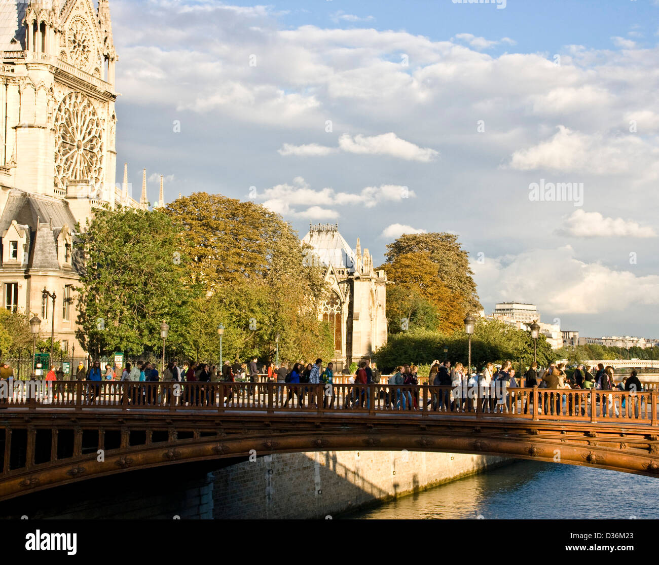 Tourists at dusk on Pont au Double river Seine Notre Dame Cathedral Paris France Europe - Stock Image
