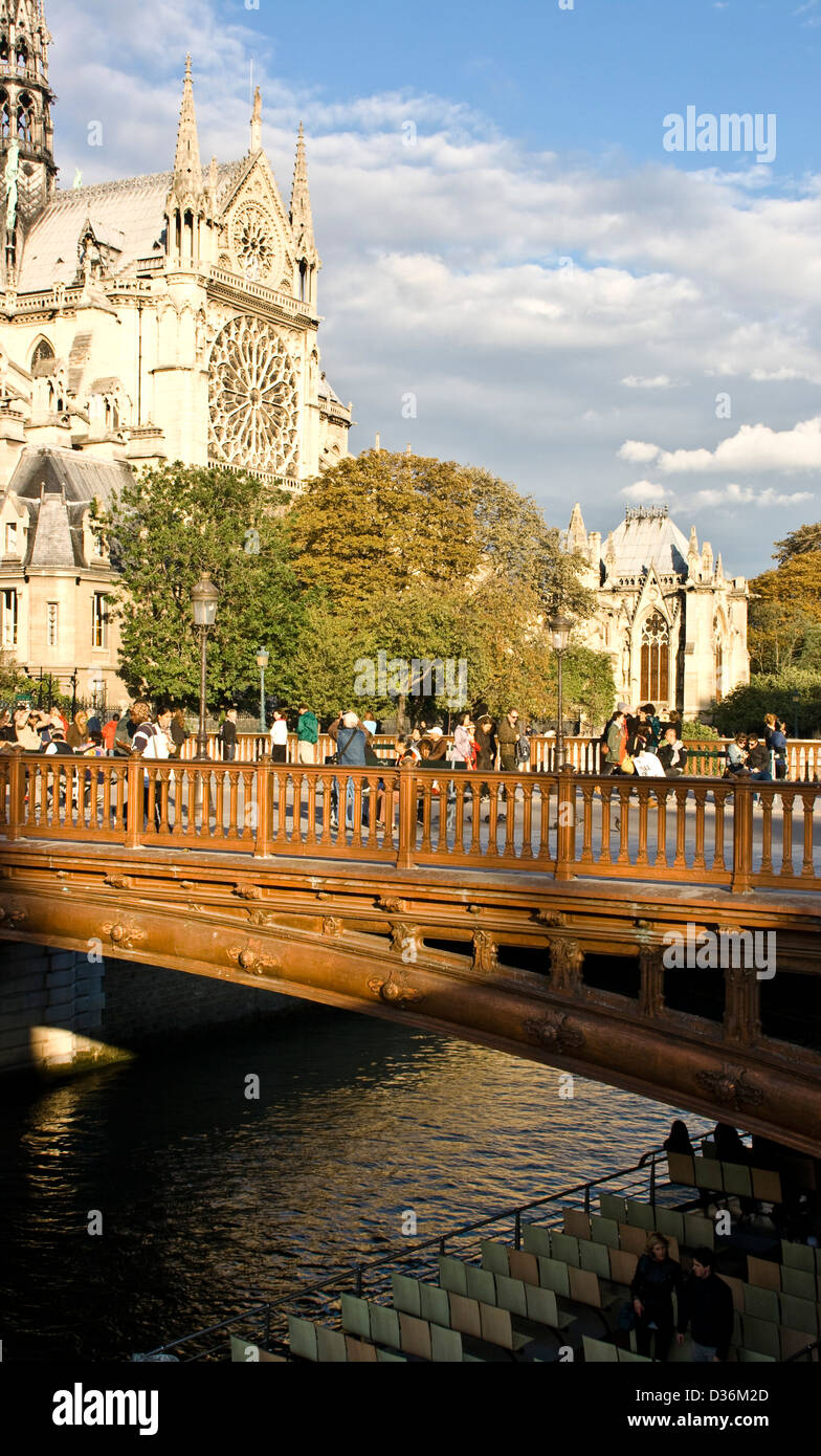 Tourists in dusk sunset sunlight on Pont au Double river Seine Notre Dame Cathedral Paris France Europe - Stock Image