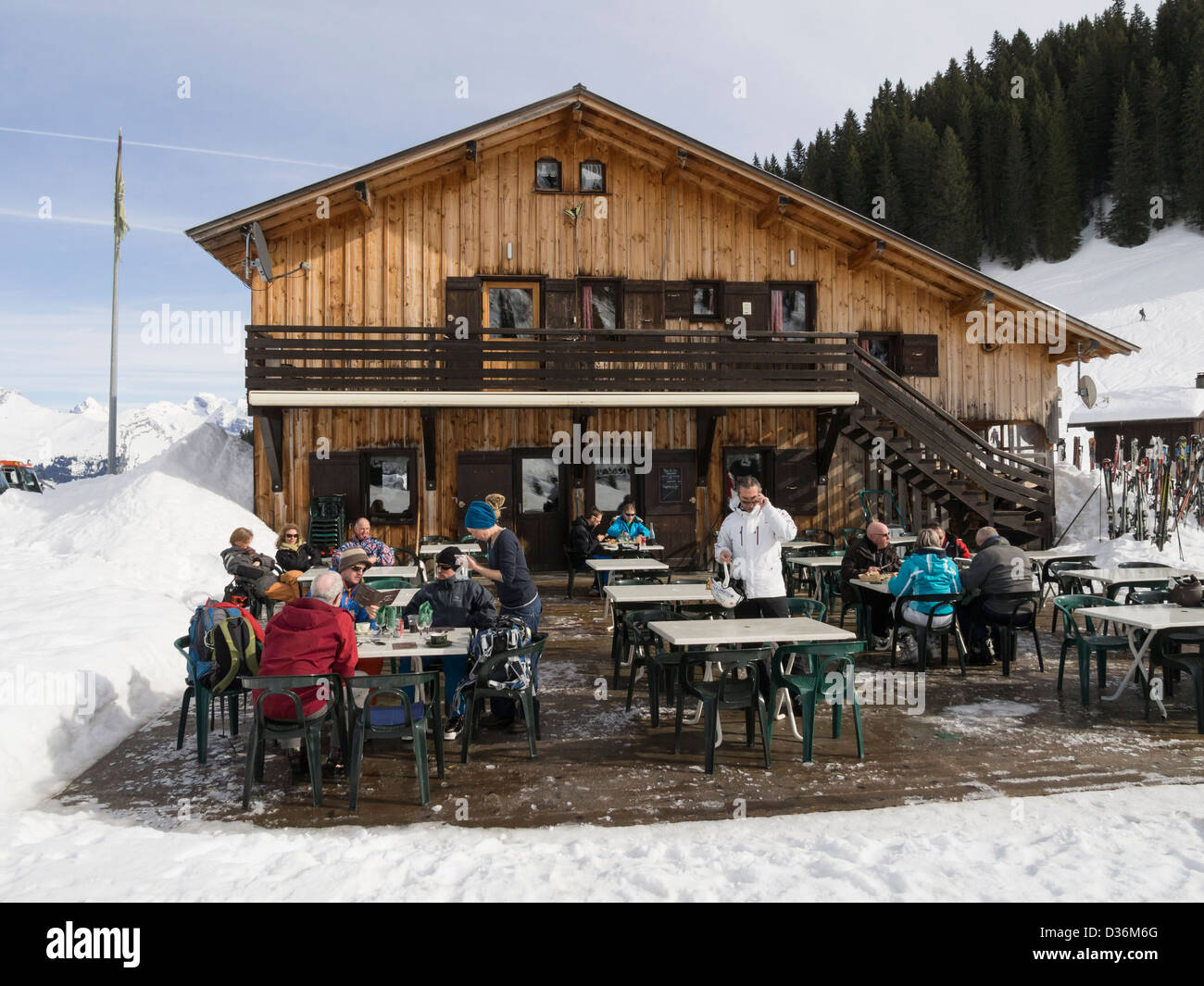 People dining outside Gite du Lac de Gers alpine lakeside ski restaurant in Le Grand Massif in French Alps. Sixt - Stock Image