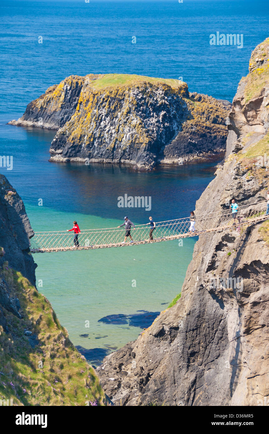 Tourists crossing the Carrick a rede rope bridge to Carrick island Ballycastle County Antrim Northern Ireland UK Stock Photo