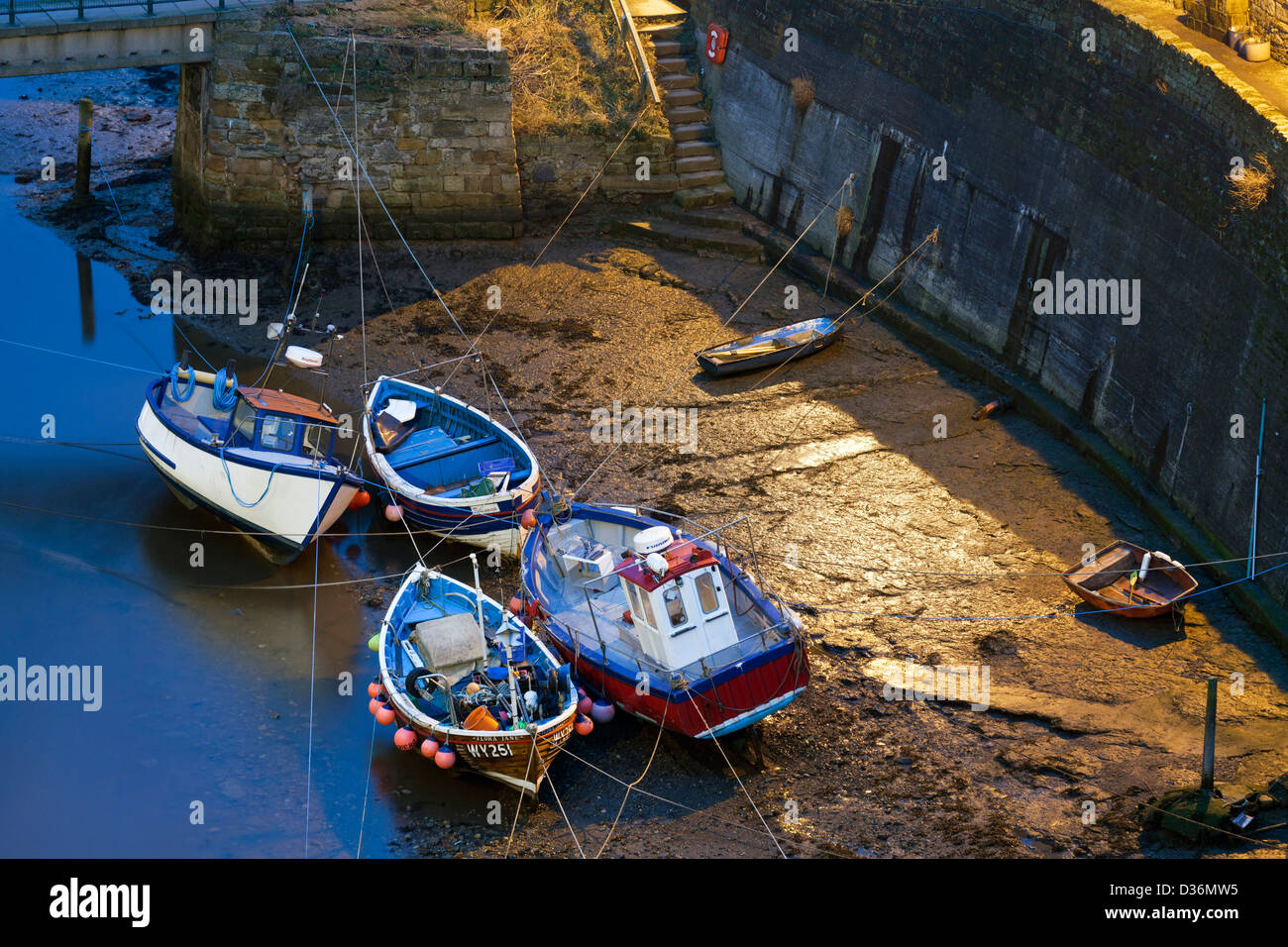 Fishing boats moored at Staithes, after dark. - Stock Image