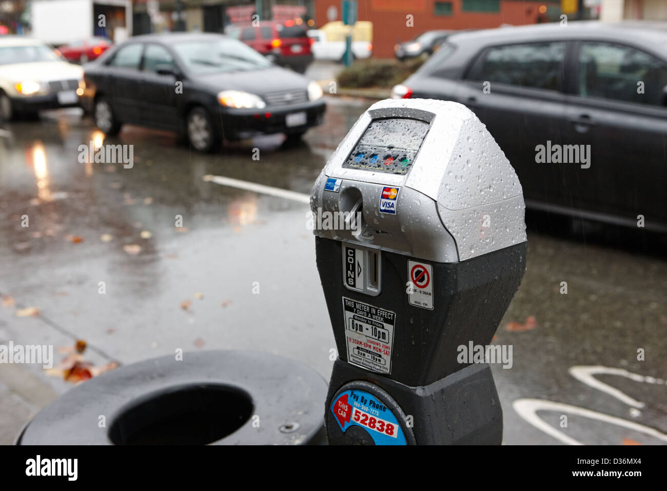 water soaked coin and credit card parking meter on the streets of downtown Vancouver BC Canada - Stock Image